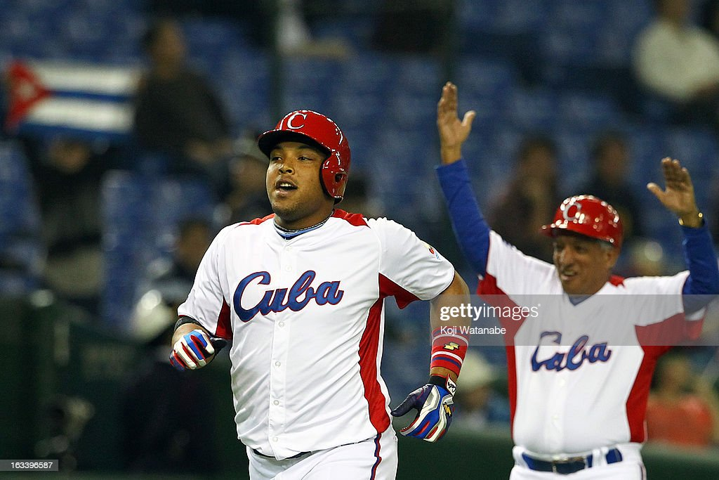 Outfielder Yasmany Tomas #27 of Cuba (L) celebrates after scoring hits a three run home run in the top half of the sixth inning during the World Baseball Classic Second Round Pool 1 game between Chinese Taipei and Cuba at Tokyo Dome on March 9, 2013 in Tokyo, Japan.