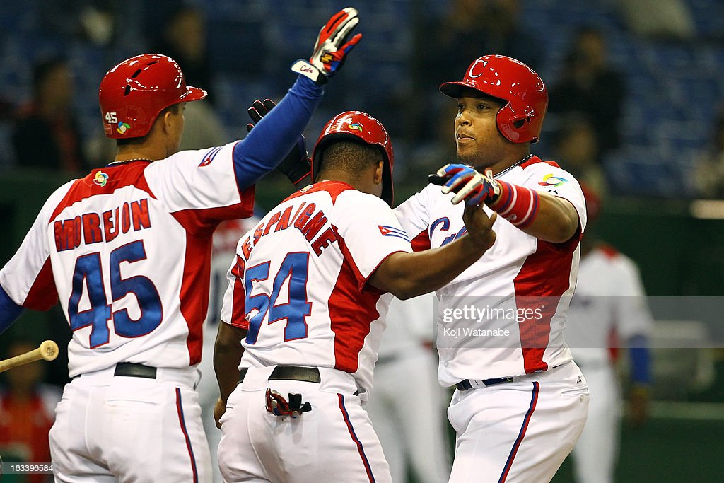 Outfielder Yasmany Tomas #27 of Cuba celebrates with team-mates after scoring hits a three run home run in the top half of the sixth inning during the World Baseball Classic Second Round Pool 1 game between Chinese Taipei and Cuba at Tokyo Dome on March 9, 2013 in Tokyo, Japan.