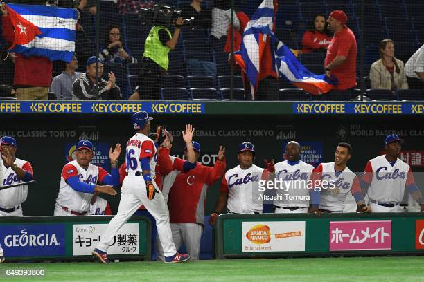 Outfielder Yoelkis Cespedes of Cuba high fives with his team mates after scoring a run by a tworun triple of outfielder Roel Santos to make it 03 in...
