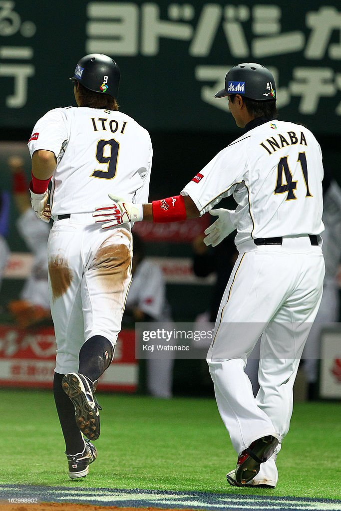 Outfielder Yoshio Itoi and Infielder Atsunori Inaba of Japan celebrates after scoring in the bottom half of the third inning during the World...