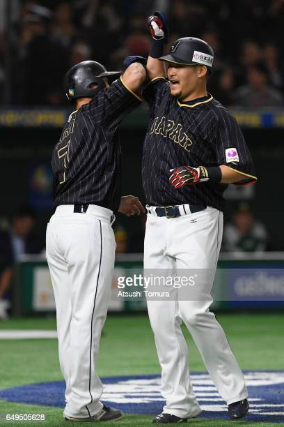 Outfielder Yoshitomo Tsutsugoh of Japan celebrates with his team mate Norichika Aoki after hitting a tworun homer in the top of the eighth inning...