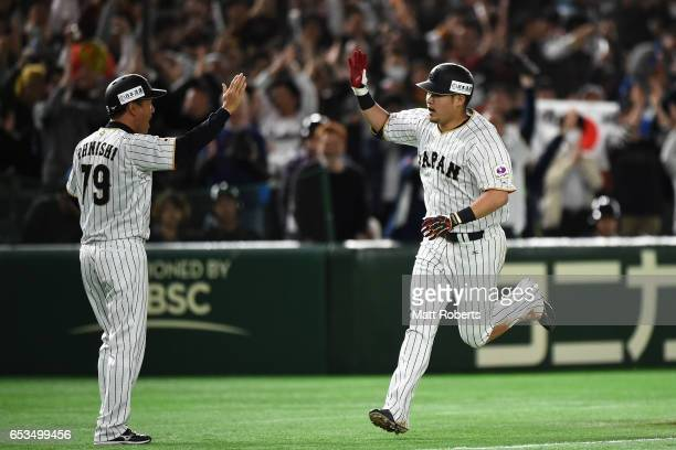 Outfielder Yoshitomo Tsutsugoh of Japan celebrates hitting a solo homerun with coach Takayuki Onishi to make it 01 in the bottom of the sixth inning...