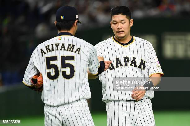Outfielder Yoshitomo Tsutsugoh of Japan high fives with Outfielder Shogo Akiyama after hitting a RBI single to make it 44 after the bottom of the...