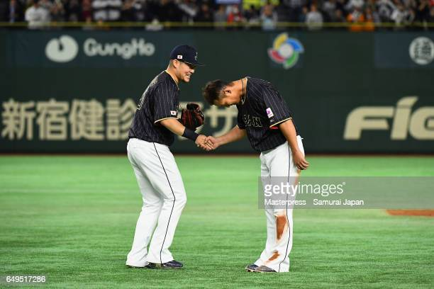 Outfielder Yoshitomo Tsutsugoh shakes hands with Infielder Sho Nakata of Japan after the top of the eighth inning during the World Baseball Classic...