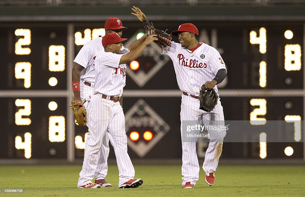 Outfielders <a gi-track='captionPersonalityLinkClicked' href=/galleries/search?phrase=Ben+Revere&family=editorial&specificpeople=6826641 ng-click='$event.stopPropagation()'>Ben Revere</a> #2, <a gi-track='captionPersonalityLinkClicked' href=/galleries/search?phrase=Domonic+Brown&family=editorial&specificpeople=6900643 ng-click='$event.stopPropagation()'>Domonic Brown</a> #9 and <a gi-track='captionPersonalityLinkClicked' href=/galleries/search?phrase=Marlon+Byrd&family=editorial&specificpeople=217377 ng-click='$event.stopPropagation()'>Marlon Byrd</a> #3 of the Philadelphia Phillies react after a win 4-3 over the Pittsburgh Pirates on September 9, 2014 at Citizens Bank Park in Philadelphia, Pennsylvania.