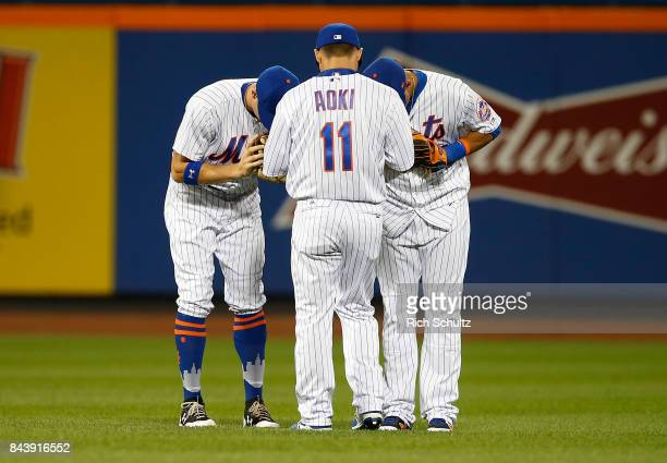 Outfielders Brandon Nimmo and Juan Lagares bow to Norichika Aoki of the New York Mets after defeating the Cincinnati Reds 72 during a game at Citi...