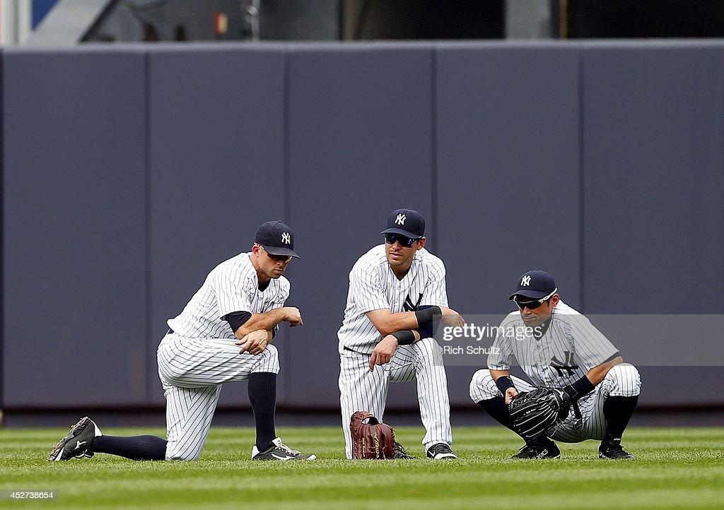 Outfielders <a gi-track='captionPersonalityLinkClicked' href=/galleries/search?phrase=Brett+Gardner&family=editorial&specificpeople=4172518 ng-click='$event.stopPropagation()'>Brett Gardner</a> #11, <a gi-track='captionPersonalityLinkClicked' href=/galleries/search?phrase=Jacoby+Ellsbury&family=editorial&specificpeople=4172583 ng-click='$event.stopPropagation()'>Jacoby Ellsbury</a> #22 and <a gi-track='captionPersonalityLinkClicked' href=/galleries/search?phrase=Ichiro+Suzuki&family=editorial&specificpeople=201556 ng-click='$event.stopPropagation()'>Ichiro Suzuki</a> #31of the New York Yankees gather during a pitching change in the seventh inning against the Toronto Blue Jays during an MLB baseball game at Yankee Stadium on July 26, 2014 in the Bronx borough of New York City. The Blue Jays defeated the Yankees 6-4.