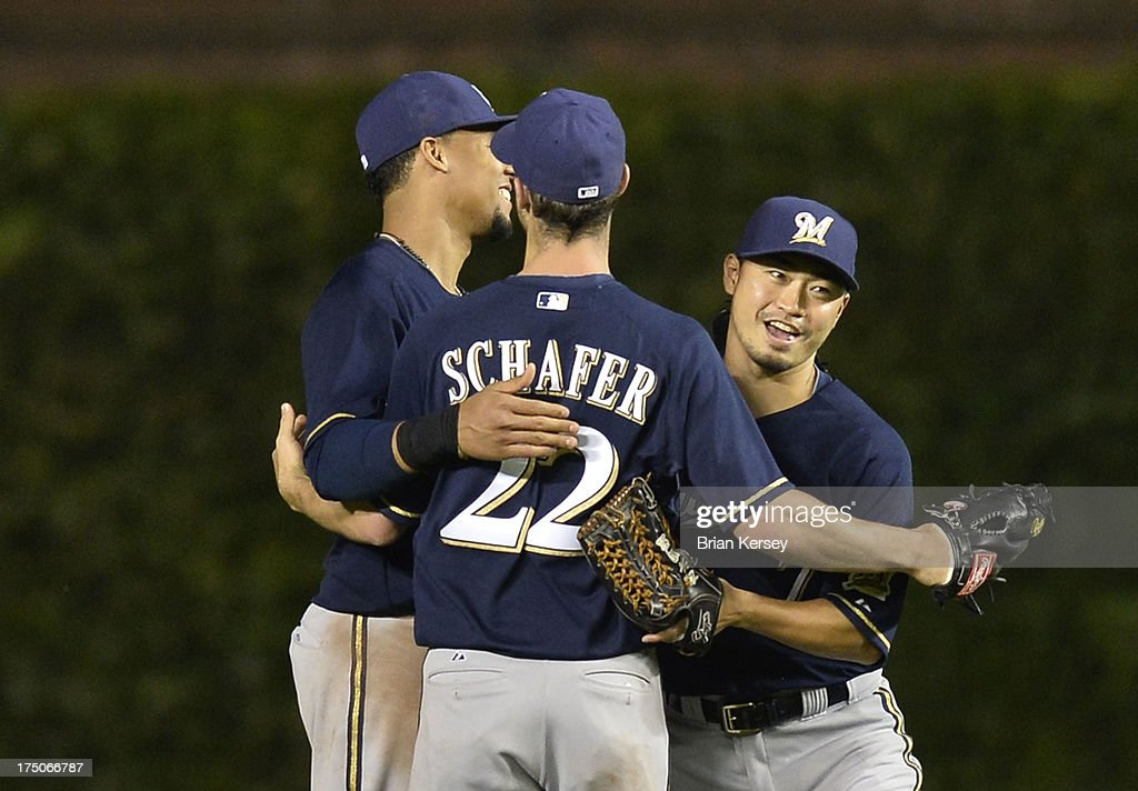 Outfielders Carlos Gomez #27 (L-R), Logan Schafer #22 and Norichika Aoki #7 of the Milwaukee Brewers celebrate their win in Game Two of a double header against the Chicago Cubs at Wrigley Field on July 30, 2013 in Chicago, Illinois. The Brewers defeated the Cubs 3-2.