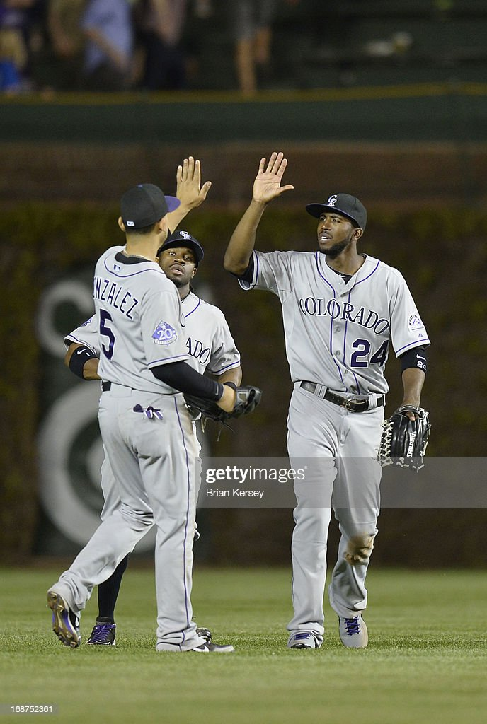 Outfielders Carlos Gonzalez #5, Eric Young Jr. #1 and <a gi-track='captionPersonalityLinkClicked' href=/galleries/search?phrase=Dexter+Fowler&family=editorial&specificpeople=4949024 ng-click='$event.stopPropagation()'>Dexter Fowler</a> #24 of the Colorado Rockies celebrate a win over the Chicago Cubs on May 14, 2013 at Wrigley Field in Chicago, Illinois. The Rockies defeated the Cubs 9-4.