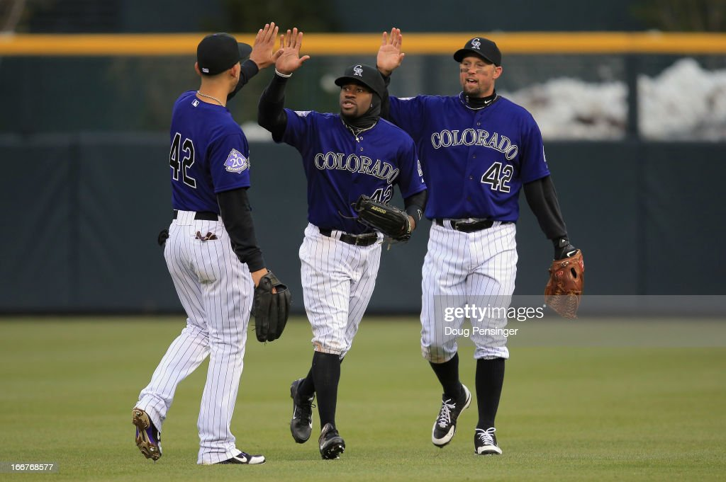 Outfielders Carlos Gonzalez, Eric Young Jr. and <a gi-track='captionPersonalityLinkClicked' href=/galleries/search?phrase=Michael+Cuddyer&family=editorial&specificpeople=208127 ng-click='$event.stopPropagation()'>Michael Cuddyer</a> of the Colorado Rockies celebrate their 8-4 victory over the New York Mets at Coors Field on April 16, 2013 in Denver, Colorado. All uniformed team members are wearing jersey number 42 in honor of Jackie Robinson Day.