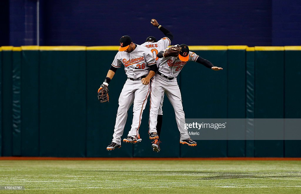 Outfielders Chris Dickerson #36, Adam Jones #10 and <a gi-track='captionPersonalityLinkClicked' href=/galleries/search?phrase=Nick+Markakis&family=editorial&specificpeople=614708 ng-click='$event.stopPropagation()'>Nick Markakis</a> #21 of the Baltimore Orioles celebrate victory over the Tampa Bay Rays at Tropicana Field on June 9, 2013 in St. Petersburg, Florida.