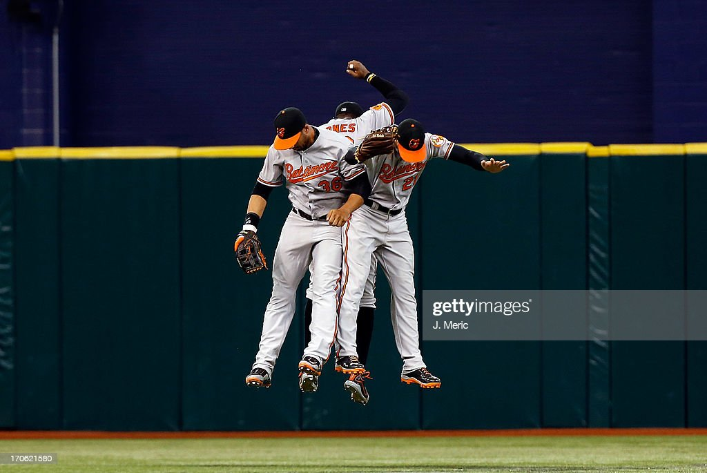 Outfielders Chris Dickerson #36, Adam Jones #10 and Nick Markakis #21 of the Baltimore Orioles celebrate victory over the Tampa Bay Rays at Tropicana Field on June 9, 2013 in St. Petersburg, Florida.