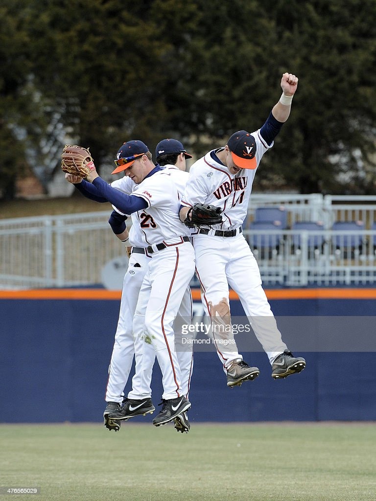 Outfielders Derek Fisher #23, Brandon Downes #10 and Joe McCarthy #31 of the University of Virginia Cavaliers leep high in the air to celebrate a victury after a game on March 1, 2014 against the Monmouth University Hawks at Davenport Field on the campus of the University of Virginia in Charlottesville, VA. The Cavaliers beat the Hawks, 6-3.
