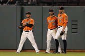 Outfielders Gregor Blanco Angel Pegan and Hunter Pence of the San Francisco Giants talk while they wait during a pitching change in the ninth inning...
