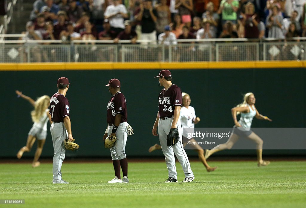 Outfielders Jacob Robson #7, Derrick Armstrong #6, and Hunter Renfroe #34 of the Mississippi State Bulldogs watch as three young women interupt play by running onto the field during the eighth inning as the play the UCLA Bruins during game two of the College World Series Finals on June 25, 2013 at TD Ameritrade Park in Omaha, Nebraska. UCLA won 8-0 to take the series two games to none and win the College World Series Championship.