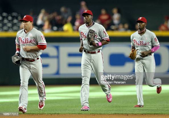 Outfielders Laynce Nix John Mayberry Jr #15 and Domonic Brown of the Philadelphia Phillies following the MLB game against the Arizona Diamondbacks at...