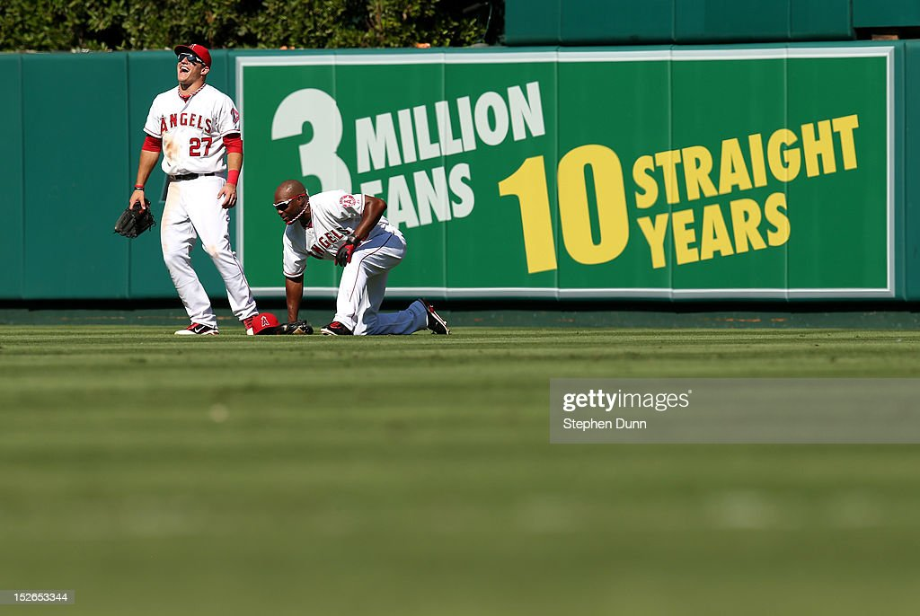 Outfielders <a gi-track='captionPersonalityLinkClicked' href=/galleries/search?phrase=Mike+Trout&family=editorial&specificpeople=7091306 ng-click='$event.stopPropagation()'>Mike Trout</a> #27 and <a gi-track='captionPersonalityLinkClicked' href=/galleries/search?phrase=Torii+Hunter&family=editorial&specificpeople=183408 ng-click='$event.stopPropagation()'>Torii Hunter</a> #48 of the Los Angeles Angels of Anaheim have a laugh in the outfield in front of a sign celebrating the Angels' tenth consecutive three million attendance season during a pitching change in the ninth inning against the Chicago White Sox at Angel Stadium of Anaheim on September 23, 2012 in Anaheim, California. The Angels won 4-1.