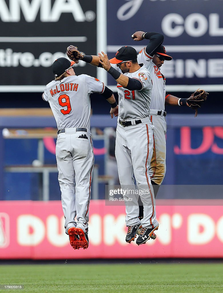 Outfielders Nate McLouth #9, Nick Markakis #21 and Adam Jones #10 of the Baltimore Orioles celebrate after the Orioles defeated the New York Yankees 7-3 in a MLB baseball game at Yankee Stadium on September 1, 2013 in the Bronx borough of New York City.
