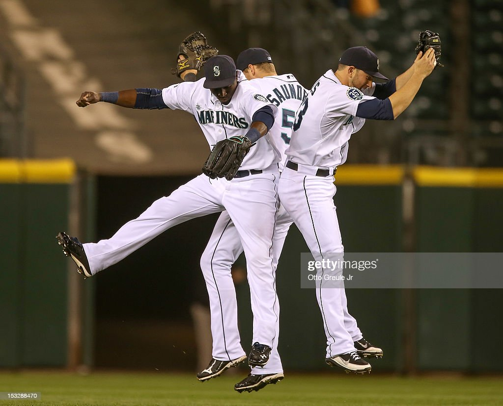 Outfielders Trayvon Robinson #12, Michael Saunders #55, and Casper Wells #33 of the Seattle Mariners celebrate after defeating the Los Angeles Angels of Anaheim 6-1 at Safeco Field on October 2, 2012 in Seattle, Washington.