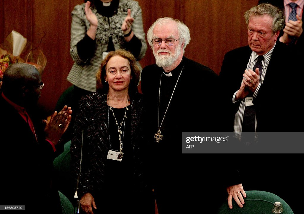 Outgoing Archbishop of Canterbury Rowan Williams (CR) and his wife Jane (CL) receive applaus after he gave his farewell speech during the General Synod of the Church of England, at Church House in central London on November 21, 2012. The Church of England has 'undoubtedly' lost credibility after voting to reject the appointment of women bishops, its leader the Archbishop of Canterbury said on November 21.