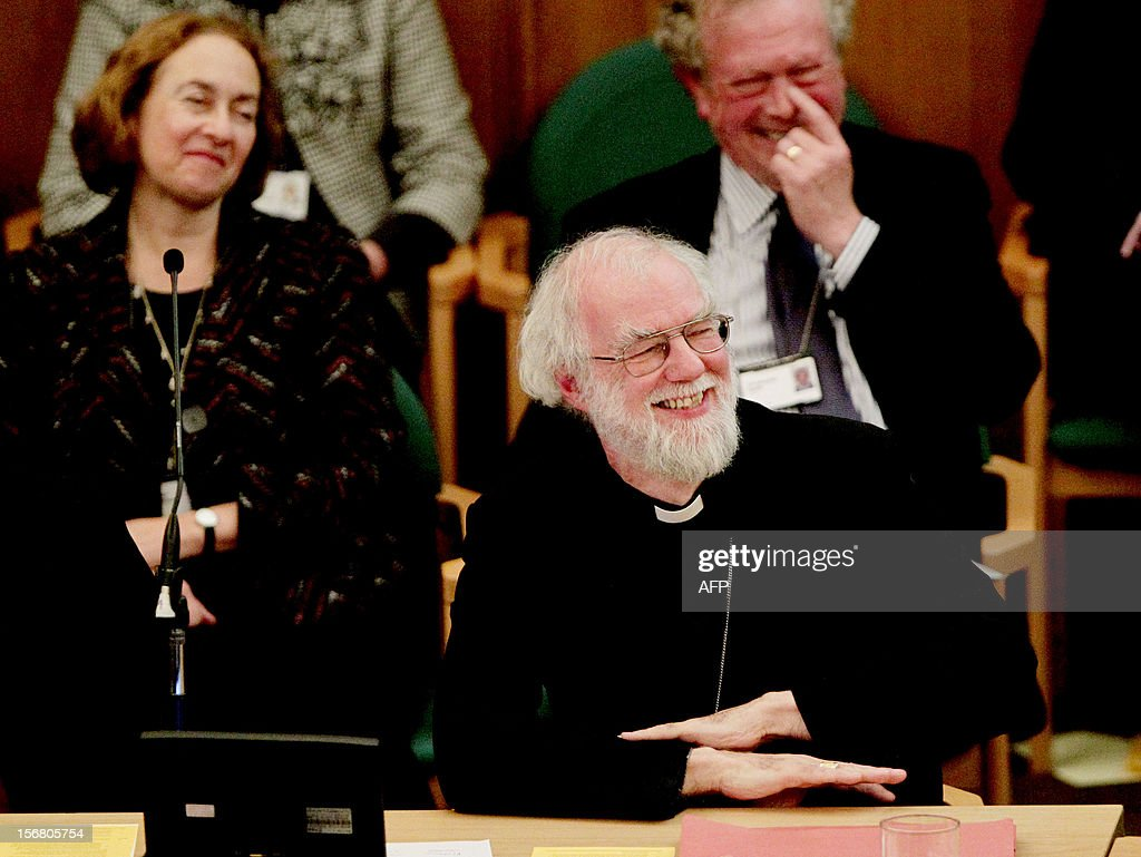 Outgoing Archbishop of Canterbury Rowan Williams (R) smiles during a meeting at the General Synod of the Church of England, at Church House in central London on November 21, 2012. The Church of England has 'undoubtedly' lost credibility after voting to reject the appointment of women bishops, its leader the Archbishop of Canterbury said on November 21. AFP PHOTO / POOL / YUI MOK