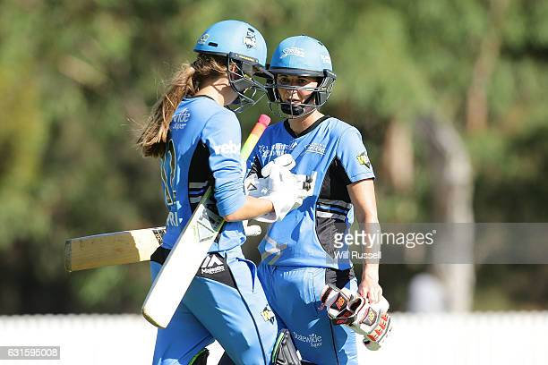 Outgoing batswoman Charlotte Edwards of the Strikers speaks to incoming batswoman Alex Price of the Strikers during the Women's Big Bash League match...