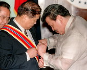 Outgoing Chinese Ambassador Guan Deng Ming receives the Order of Sikatuna Award from Philippine President Joseph Estrada for his meritorious service...