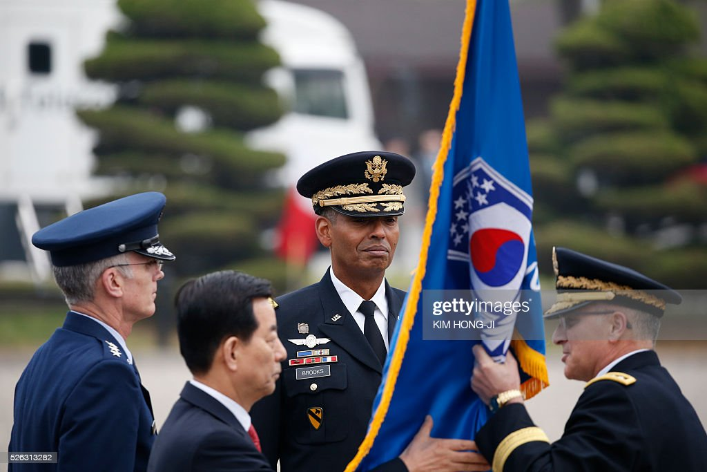 Outgoing Commander General Curtis M. Scaparrotti (R) hands the South Korea-US Combined Forces Command flag over to South Korean Defense Minister Han Min-koo (2nd L) as incoming Commander General Vincent K. Brooks (C) looks on during a change of command ceremony for the United Nations Command, Combined Forces Command, and United States Forces Korea at the US military base in Seoul on April 30, 2016. / AFP / pool / KIM