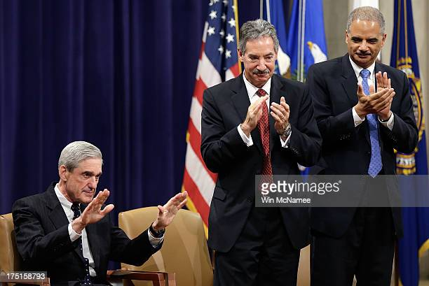 Outgoing FBI Director Robert Mueller is applauded by Deputy Attorny General James Cole and US Attorney General Eric Holder during Mueller's farewell...