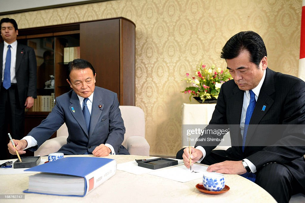 Outgoing Finance Minister Koriki Jojima (R) of Democratic Party of Japan and incoming Taro Aso of Liberal Democratic Party sign to the handover document at Finance Ministry on December 27, 2012 in Tokyo, Japan.