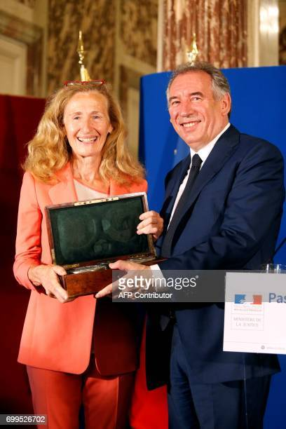 Outgoing French Minister of Justice and Leader of the French MoDem centrist party Francois Bayrou gives the box of the official seals to newly...