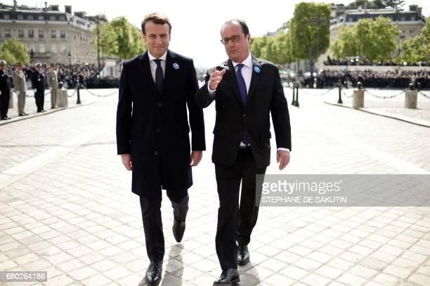 TOPSHOT Outgoing French president Francois Hollande and French presidentelect Emmanuel Macron talk as they walk during the ceremony marking the 72nd...