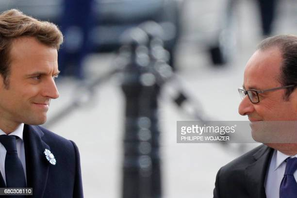 TOPSHOT Outgoing French President Francois Hollande looks at Presidentelect Emmanuel Macron as they stand at the Tomb of the Unknown Soldier at the...