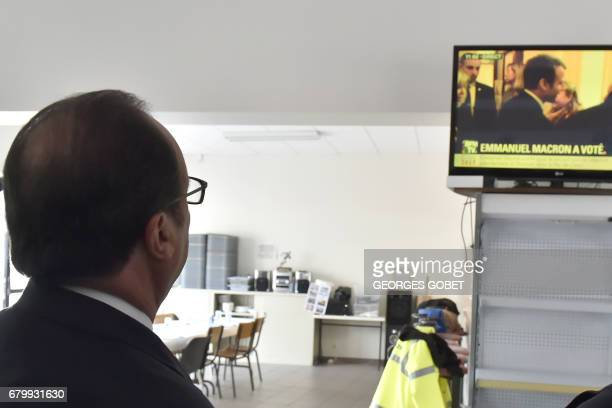 Outgoing French president Francois Hollande looks up at a television showing a French presidential election candidate after casting his votes in...