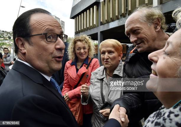 Outgoing French president Francois Hollande meets people after casting his ballot at a polling station in Tulle central France on May 7 during the...