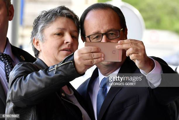 Outgoing French president Francois Hollande poses for a selfie after casting his ballot at a polling station in Tulle central France on May 7 during...
