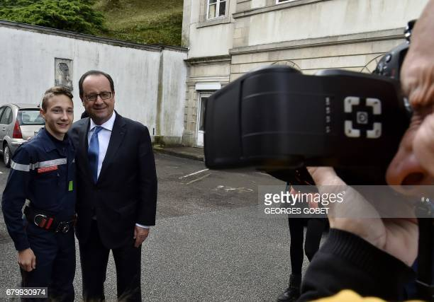 Outgoing French president Francois Hollande poses with a young firefighter after casting his ballot at a polling station in Tulle central France on...