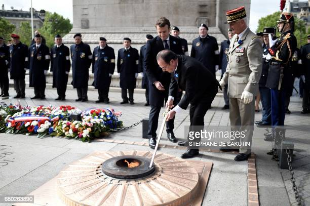 Outgoing French president Francois Hollande renews the eternal flame as French presidentelect Emmanuel Macron and President of the Committee of the...
