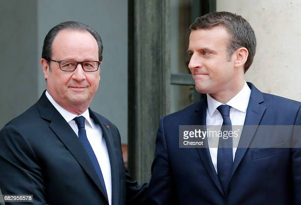Outgoing French President Francois Hollande shakes hands with newly elected French president Emmanuel Macron prior to a handover ceremony at the...