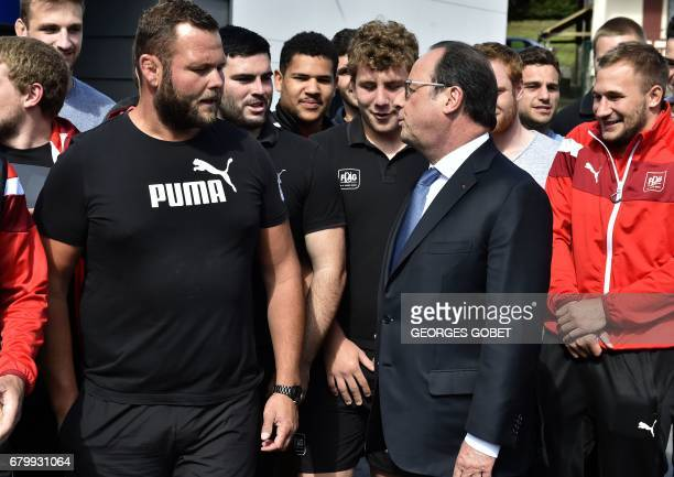 Outgoing French President Francois Hollande speaks to athletes as he visits polling stations after casting his ballot in Tulle central France on May...