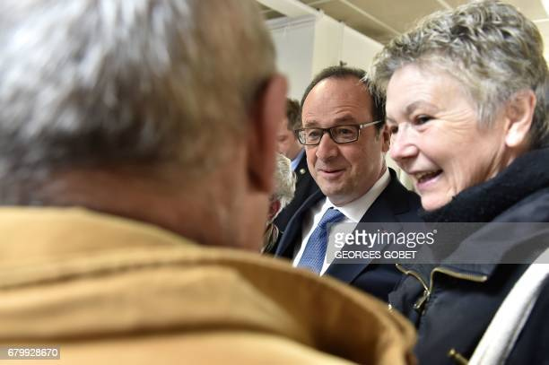 Outgoing French president Francois Hollande speaks with supporters after casting his vote in Tulle central France on May 7 in the second round of the...