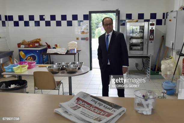 TOPSHOT Outgoing French president Francois Hollande visits a kitchen in a sports center after casting his ballot at a polling station in Tulle...