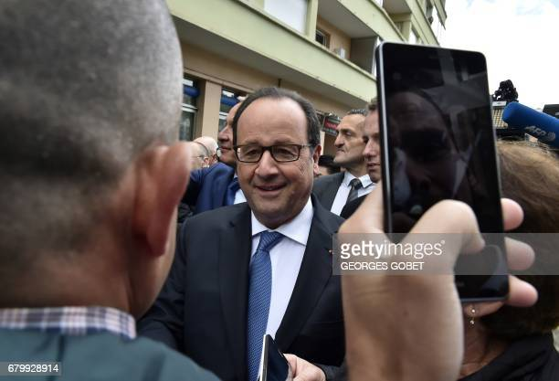 Outgoing French president Francois Hollande walks amid supporters after casting his ballot at a polling station in Tulle central France on May 7...