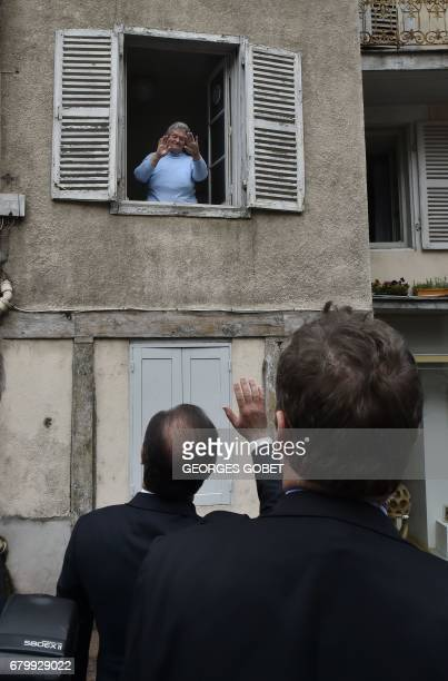 Outgoing French President Francois Hollande waves to a woman standing in a window as he visits polling stations after casting his ballot in Tulle...