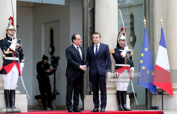 Outgoing French President Francois Hollande welcomes newly elected French president Emmanuel Macron prior to a handover ceremony at the Elysee...