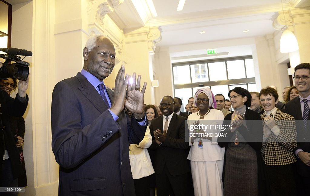 Outgoing General Secretary of the International Organisation of Francophonie (IOF) and former Senegalese president Abdou Diouf (L) is applauded as he leaves the IOF headquarters in Paris, on January 5, 2015.
