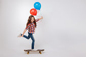 Sharing positive atmosphere. Active skilled artistic girl smiling and holding balloons while standing against white background and using skateboard