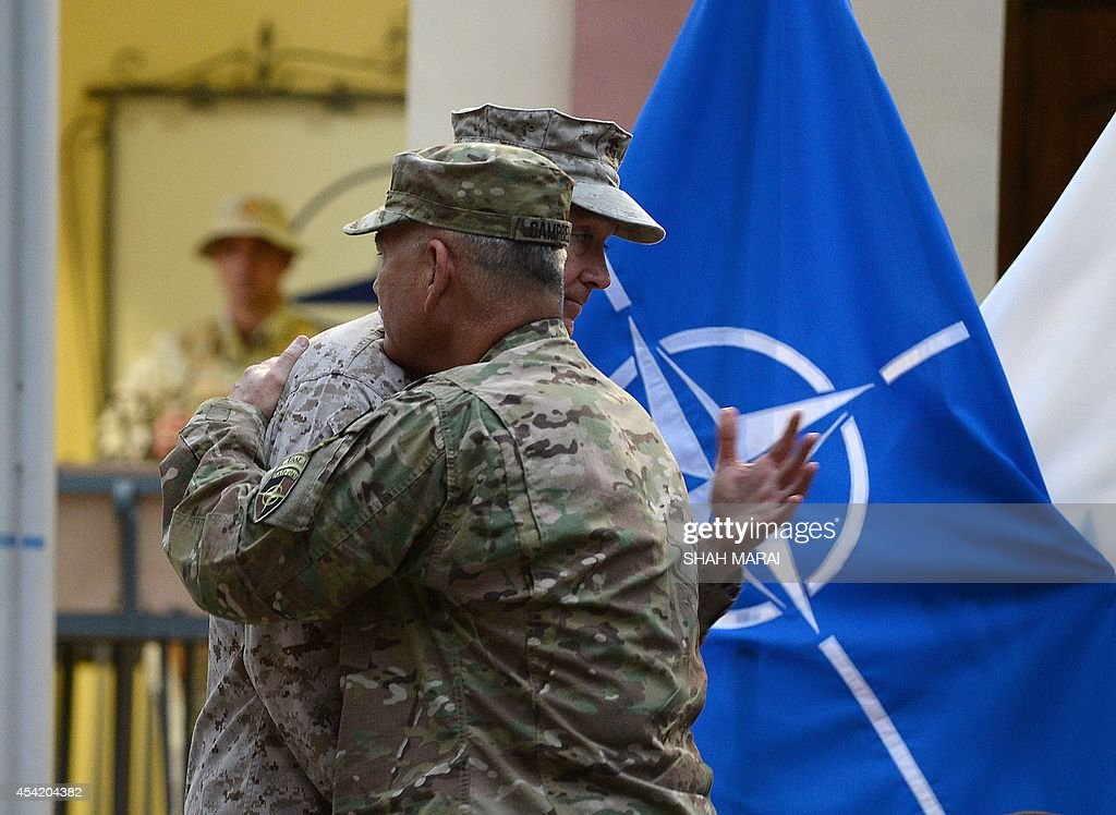 Outgoing International Security Assistance Force (ISAF) commander US General Joseph Dunford (L) hugs US Army General James Campbell (R) during a change of command ceremony at the ISAF headquarters in Kabul on August 26, 2014. US Army General James Campbell assumed command of NATO forces in Afghanistan on August 26, taking over from US General Joseph Dunford as the coalition prepares to withdraw the bulk of its combat troops by this year. AFP PHOTO/SHAH Marai