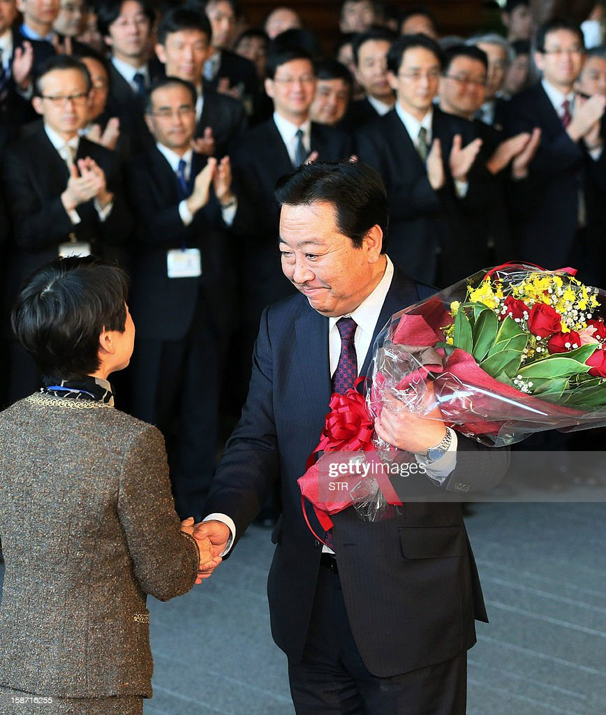 Outgoing Japanese Prime Minister Yoshihiko Noda (C) receives a flower bouquet from a member of his office staff as he leaves his official residence in Tokyo on December 26, 2012. Noda resigned his post and conservative opposition leader Shinzo Abe is to be named as Japan's new prime minister, after he swept to power on a hawkish platform of getting tough on diplomacy while fixing the economy.