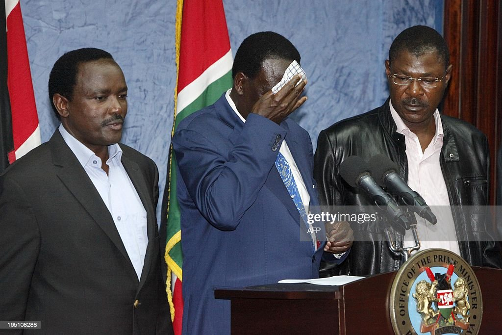 Outgoing Kenyan Prime Minister Raila Odinga (C), flanked by Kalonzo Musyoka (L), Kenya's outgoing vice president and Odinga's running mate, and Kenyan politician Moses Wetangula, wipes his forehead as he addresses the media at a press conference at his office in Nairobi on March 30, 2013. The Kenyan Supreme Court ruled on March 30 on a petition by outgoing Kenyan Prime Minister Raila Odinga challenging the election of contender Uhuru Kenyatta during the March 4 elections. The Supreme Court upheld the victory of Uhuru Kenyatta in the March 4 election, said Chief Justice Willy Mutunga. Odinga conceded defeat and wished Uhuru Kenyatta well in running the affairs of government. AFP PHOTO / Till Muellenmeister